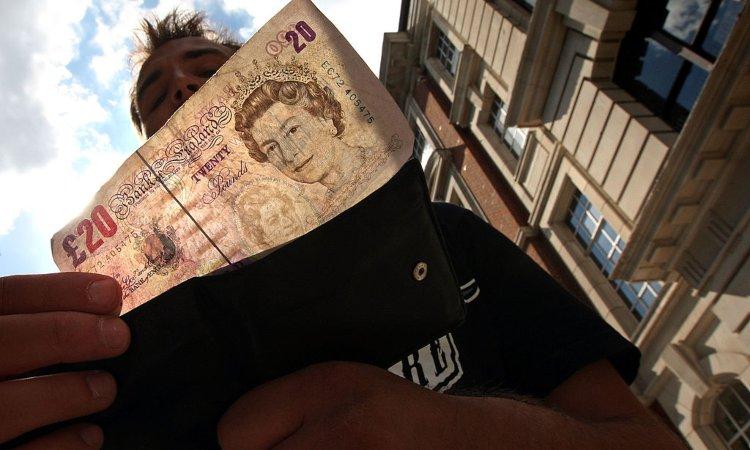 Un uomo a Londra prende una banconota da 20 pound