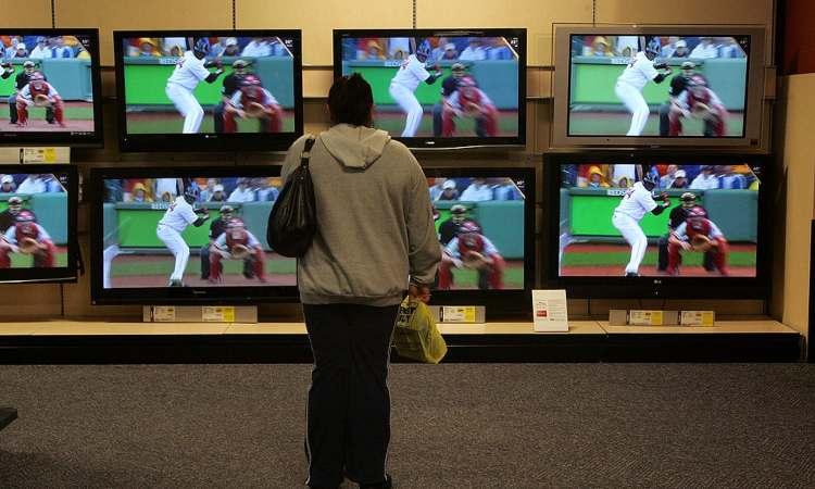 Una persona mentre guarda alcune tv sintonizzate sul baseball